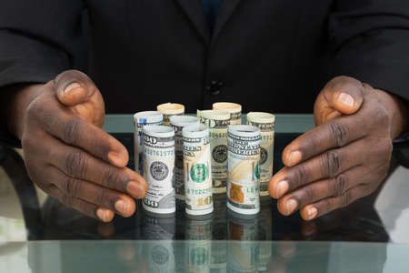 american money: Close-up Of Businessman Hands Protecting Banknotes At Glass Desk Stock Photo
