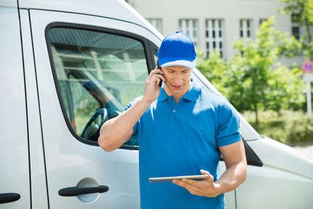 ciężarówka: Mężczyzna pracownik w Truck Przód Korzystanie z telefonu komórkowego podczas patrzenia na cyfrowym tablecie