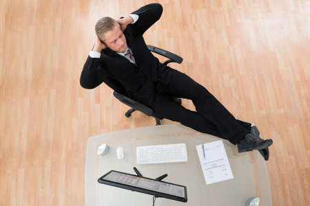 high chair: Young Businessman Relaxing On Chair In Office Stock Photo