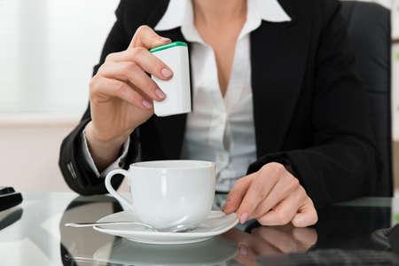 filizanka kawy: Close-up młodych businesswoman wprowadzenie cukru w filiżance Na Biurko Szklane
