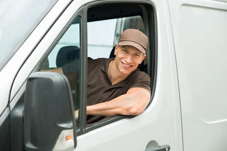 vans: Young Happy Delivery Man Driving Service Delivery Van