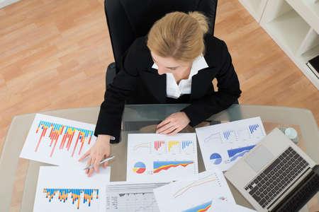 personas trabajando en oficina: Empresaria joven Analizando los gráficos financieros en lugar de trabajo Foto de archivo