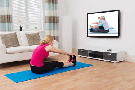 ejercicio: Mujer joven que ejercita Mientras Programa de Observaci�n en la televisi�n en el hogar Foto de archivo