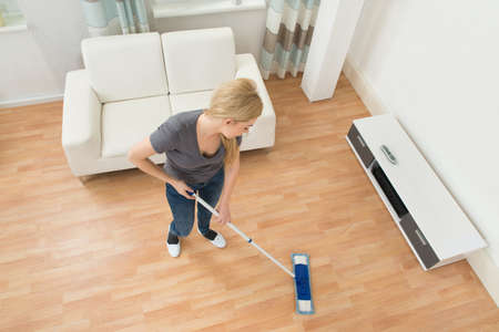 mopping: High Angle View Of Young Woman Mopping Floor At Home