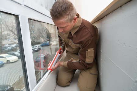 caulk: Young Male Worker Applying Glue With Silicone Gun