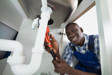 plumber tools: Young African Handyman Repairing Sink Pipe With Worktool