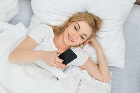 mujer en la cama: Young Happy Woman Using Mobile Phone In Bed Foto de archivo