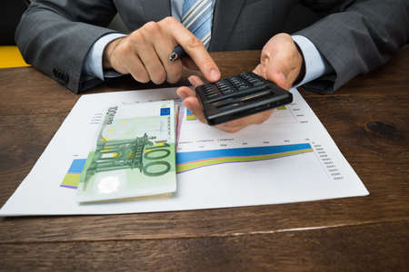 banconote euro: Close-up Of Businessperson Hands Analyzing Graph With Calculator In Office