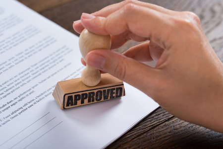 Close-up Person Hände mit Stamper On Dokument mit dem Text Genehmigt Standard-Bild