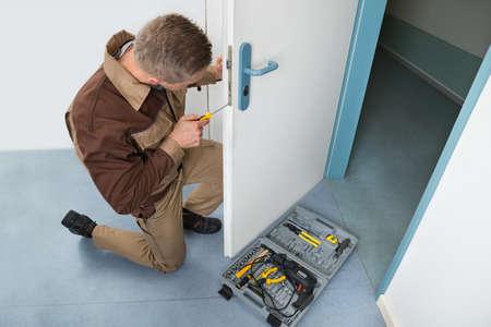 carpintero: Opinión de alto ángulo masculino Carpintero Con Destornillador Fijación cerradura de puerta
