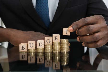 einsparung: Close-up der Geschäftsmann Hände setzen die Buchstaben des Wortes Budget Auf Stapel Münzen