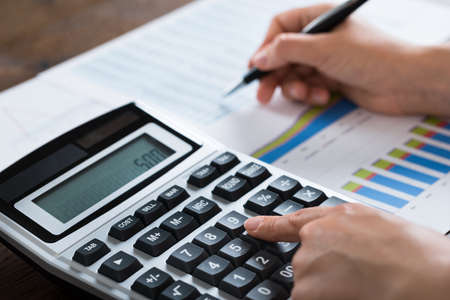 Close-up Of Businesswoman Analyzing Financial Report With Calculator At Wooden Desk