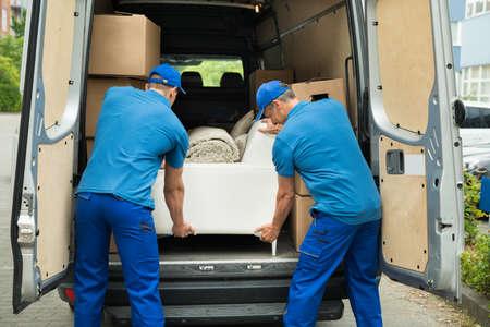 carga: Dos trabajadores hombres de uniforme azul Ajuste Sof� En Cami�n Foto de archivo