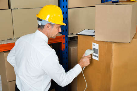 barcode scanner: Manager Scanning Label On Cardboard Box With Barcode Scanner In Warehouse Stock Photo