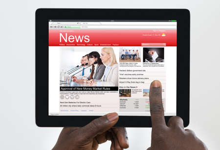 american media: Person Holding Digital Tablet With News On Screen