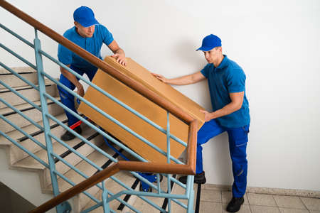 house worker: Two Male Movers Walking Downward With Box On Staircase