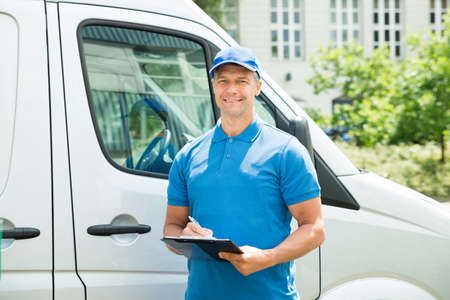 Young Happy Male Worker In Front Of Truck Writing On Clipboard Stock Photo