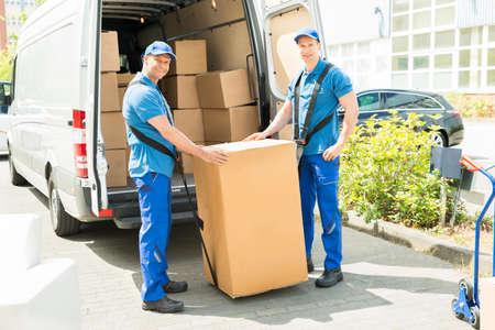 Deux Movers heureux dans uniforme bleu boîtes de chargement dans le camion de Banque d'images