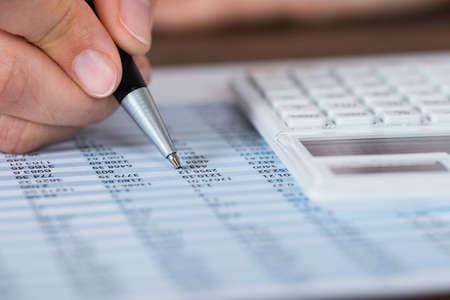 calculadora: Primer plano de la persona Manos que sostienen la pluma con la calculadora sobre informe financiero