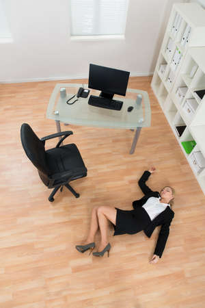 fainted: High Angle View Of Young Businesswoman Fainted On Floor In Office