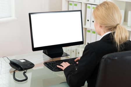 blank screen: Businesswoman Using Desktop Computer With Blank Screen At Desk