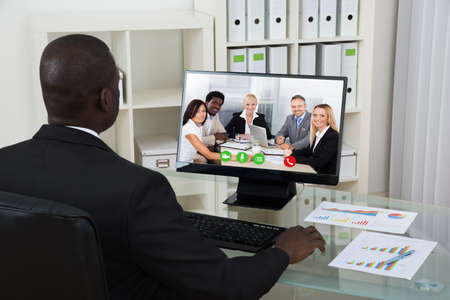 ejecutivos: Hombre de negocios africano joven chatear por video con colegas en el ordenador en la oficina Foto de archivo