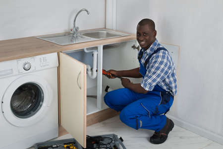 black professional: Young Happy African Male Plumber Fixing Sink In Kitchen