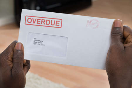 debt: Close-up Of Persons Hand Holding Overdue Notice
