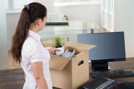 cajas de carton: Empresaria joven embalaje pertenencias en la caja de cartón en el escritorio