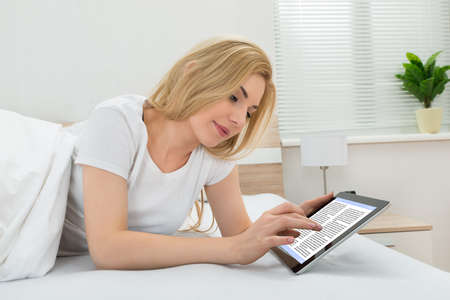 digital tablet: Young Woman Reading Ebook On Digital Tablet In Bedroom Stock Photo