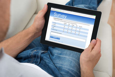 online form: Close-up Of Person On Sofa With Digital Tablet Showing Survey Form Stock Photo