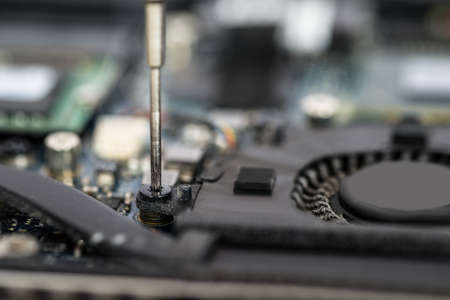Close-up Of Person Hands In Glove Repairing Laptop Motherboard