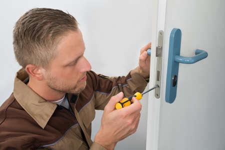 locksmith: Portrait Young Male Carpenter Repairing Door Lock