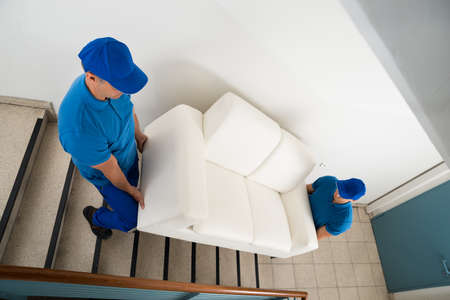 High Angle View Of Two Male Movers Carrying Sofa On Staircase Of House Archivio Fotografico