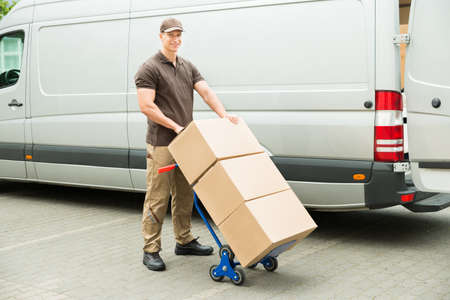 delivery box: Young Delivery Man Holding Trolley With Cardboard Boxes