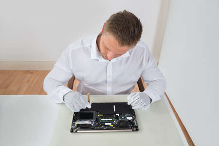 guy with laptop: Young Male Worker Repairing Laptop With Screwdriver At Desk