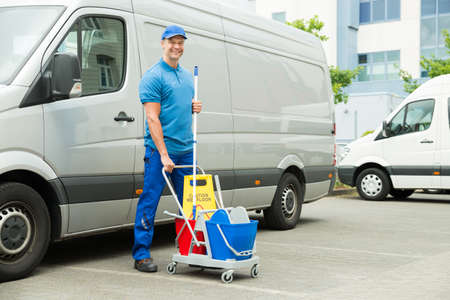 clean car: Happy Male Cleaner In Front Of Van With Cleaning Equipments