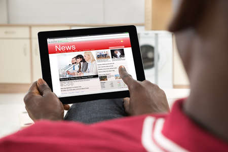 using tablet: Close-up Of African Young Man Reading News On Digital Tablet Stock Photo