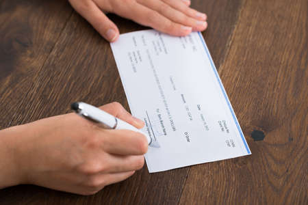banking document: Close-up Photo Of Person Hands Signing Cheque