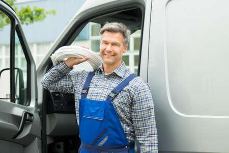overol: Reparador feliz con el cable blanco de la bobina se coloca delante de Van