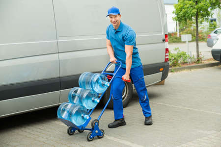 delivery service: Young Happy Delivery Man Holding Trolley With Water Bottles Stock Photo