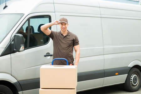 moving truck: Happy Delivery Man With Cardboard Boxes In Front Van Stock Photo