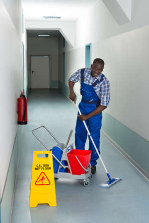 Portrait Of Young African Male Janitor Cleaning Floor In Corridor