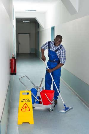 se�alizacion de seguridad: Retrato de joven africano masculino Janitor Planta Limpieza En Corredor Foto de archivo