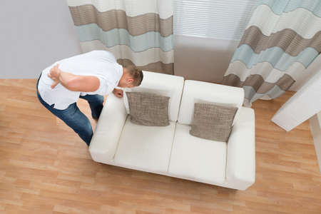 Young Man Standing Near Sofa Suffering From Back Pain
