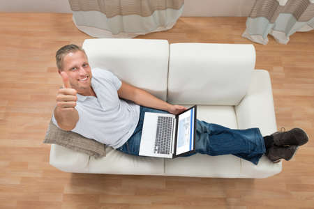 working at home: Young Happy Man Showing Thumb Up While Working On Laptop At Home Stock Photo