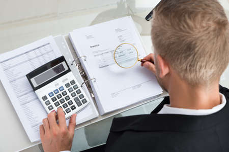 accounts: Young Businessman Checking Invoice With Magnifying Glass At Desk