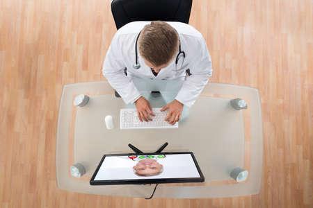 liggande: Ung doktor videochatting med senior kollega på dator vid skrivbordet Stockfoto