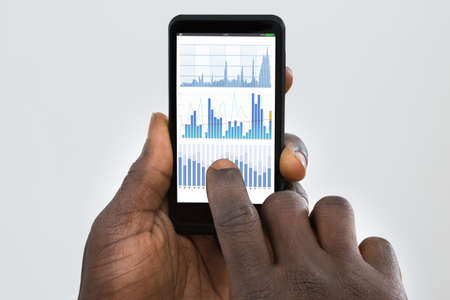black hands: Close-up Of Persons Hand Using Cellphone With Graph On Screen