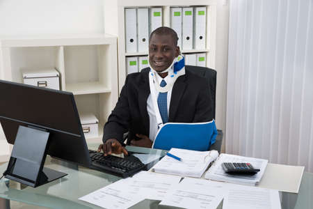 accident patient: Portrait Of Young Disabled African Businessman Working In Office Stock Photo